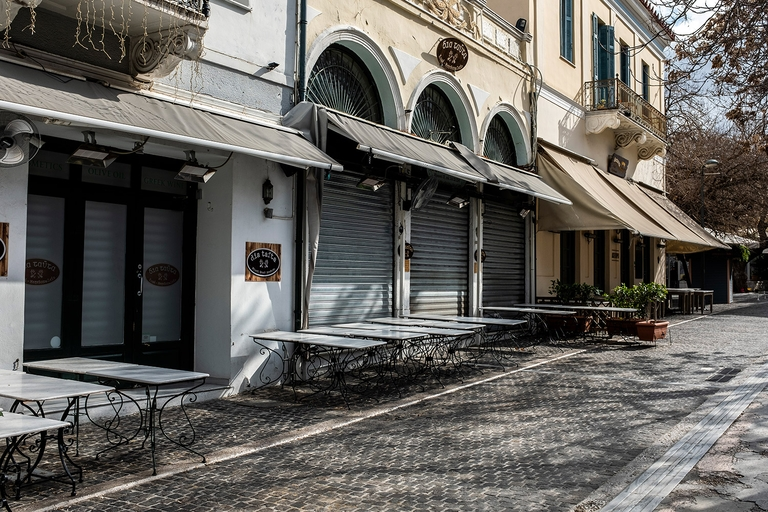 Empty tables stand in front of a closed café-restaurant in Athens, Greece on March 16, 2020. © Photo by Angelos Tzortzinis/picture alliance via Getty Images