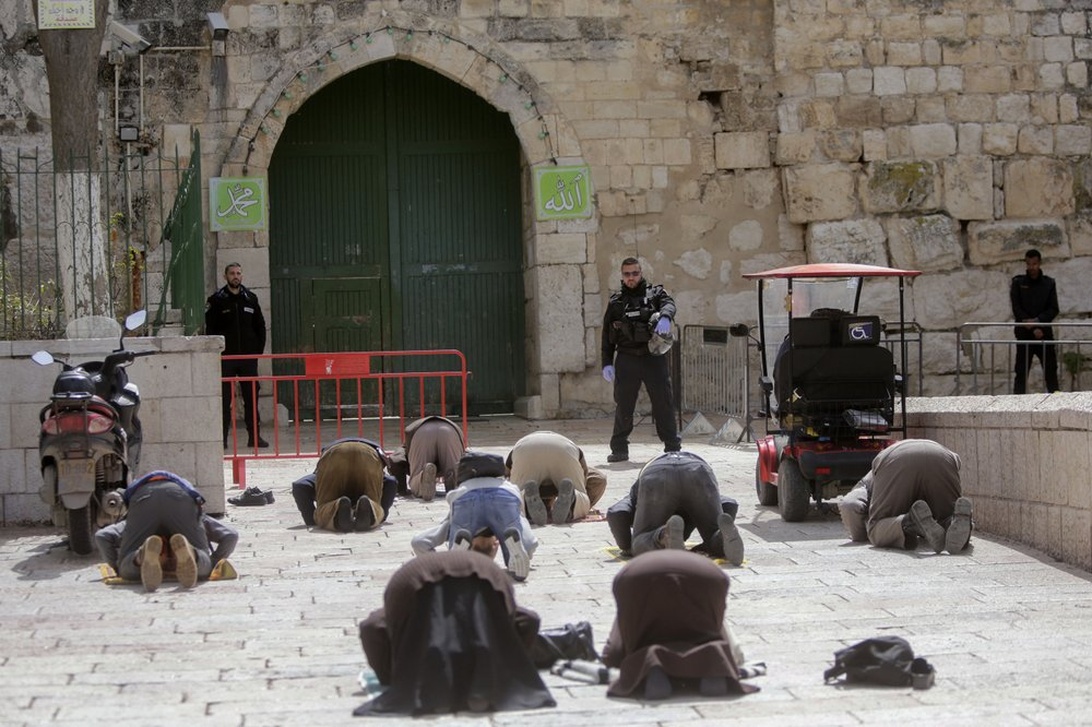 People pray in front of the shuttered gates to al-Aqsa mosque compound as all prayers are suspended to prevent the spread of coronavirus in Jerusalem, Monday, March 23, 2020. In Israel daily life has largely shut down with coronavirus cases multiplying greatly over the past week, (AP Photo/Mahmoud Illean) © AP Photo/Mahmoud Illean
