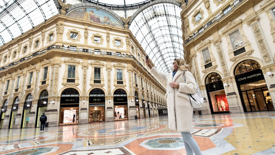 A woman wearing a protective face mask takes a selfie in Galleria Vittorio Emanuele II after a decree orders for the whole of Italy to be on lockdown in an unprecedented clampdown aimed at containing the coronavirus, in Milan, Italy, March 10, 2020. © Photo Flavio Lo Scalzo/Reuters