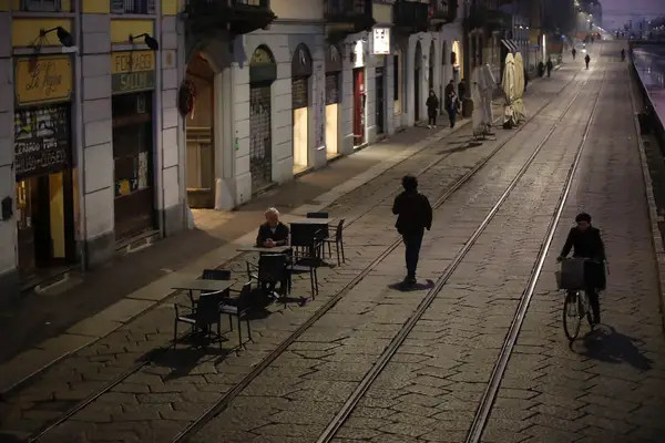 A man sits alone outside a bar at the Naviglio Grande canal in Milan, Italy, Monday, Feb. 24, 2020. © Luca Bruno / AP