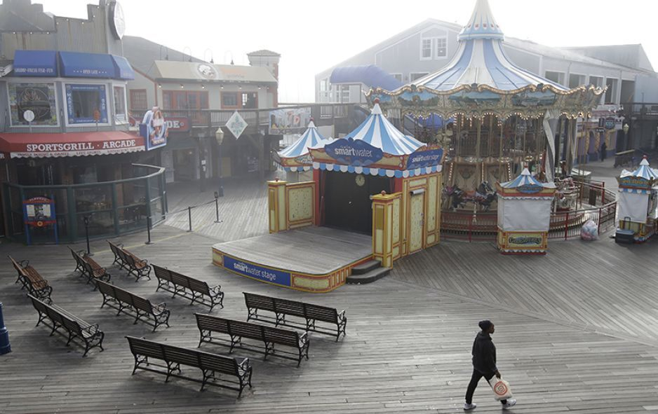 San Francisco, California: A woman walking in front of a stage and carousel at an empty Pier 39, Thursday, March 12, 2020.  © AP Photo/Jeff Chiu