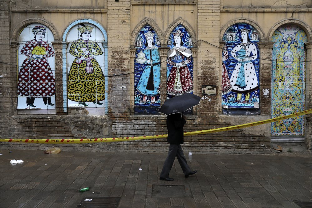 A man shelters from the rain with an umbrella a he walks past an old building decorated with replica of Iranian old paintings in a mostly empty street in a commercial district in downtown Tehran, Iran, Sunday, March 22, 2020. On Sunday, Iran imposed a two-week closure on major shopping malls and centers across the country to prevent spreading the new coronavirus. Pharmacies, supermarkets, groceries and bakeries will remain open. (AP Photo/Vahid Salemi) © AP Photo/Vahid Salemi