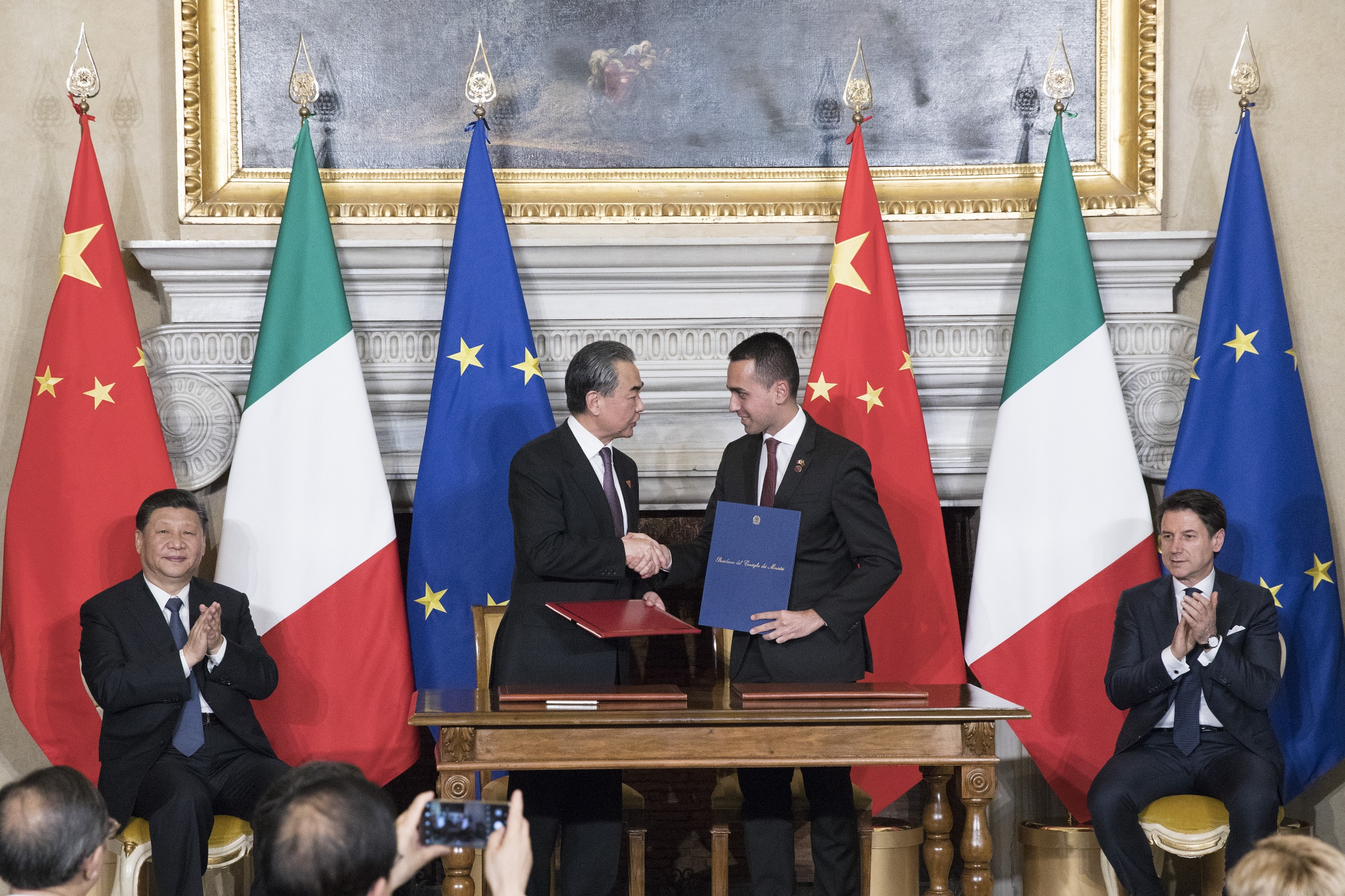 """From left, Xi Jinping, Wang Yi, Luigi Di Maio, and Giuseppe Conte, during the signing of a memorandum of understanding at Rome's Villa Madama, Saturday, March 23, 2019. Italy signed a memorandum of understanding with China on Saturday in support of Beijing's """"Belt and Road"""" initiative, which aims to weave a network of ports, bridges and power plants linking China with Africa, Europe and beyond. Is this the cause of COVID-19? © Alessia Pierdomenico/Bloomberg"""